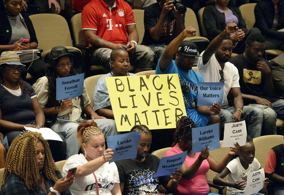 Audience members show support for speakers at a Charlotte City Council meeting concerning last week's police shooting. Photo: David T. Foster III, Associated Press
