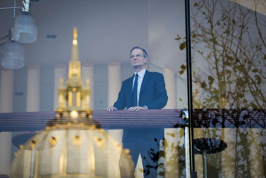 Brent Assink, the executive director of the San Francisco Symphony, looks out the window with a reflection of City Hall at Davies Symphony Hall in San Francisco. Assink plans to step down in March after 18 years at the helm of the organization. Photo: Gabrielle Lurie, The Chronicle
