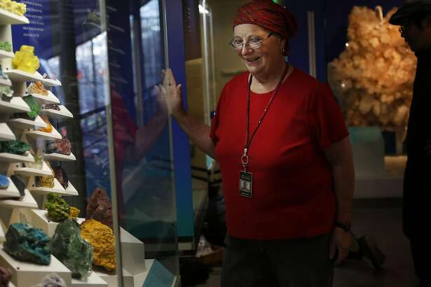 """Curator for the upcoming """"Gems and Minerals Unearthed"""" exhibit Jean DeMouthe poses for a portrait next to the colorful minerals display at the California Academy of Sciences Sept. 27, 2016 in San Francisco, Calif."""