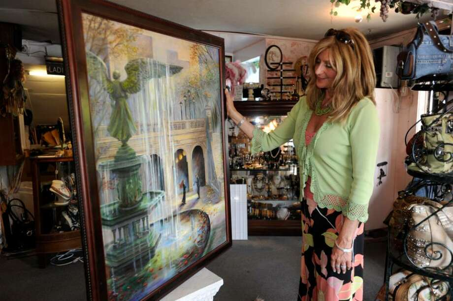 tSophia Scarpelli, owner of Sophia's on Liberty Way, in Greenwich, looks at one of the paintings by Judith Gwyn Brown that she will hang in her shop for Art to the Avenue on Tuesday, May 4, 2010. Photo: Helen Neafsey / Greenwich Time