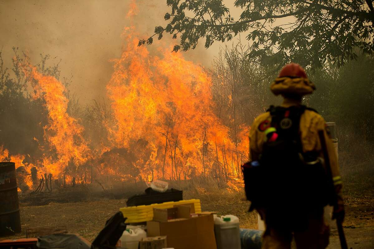 A firefighter watches flames from the Loma fire burn near Morgan Hill, Calif., on Tuesday, Sept. 27, 2016.
