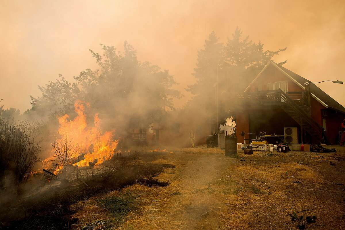 Flames from the Loma fire burn next to a home near Morgan Hill, Calif., on Tuesday, Sept. 27, 2016.