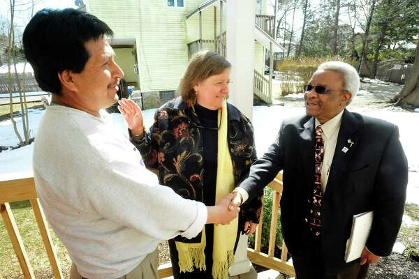 Manuel San Martin, left, thanks Fran Norman, and Wes Dupree, both of Housatonic Habitat for Humanity,  his new Danbury home, provided by Habitat, Sunday, March 10, 2013 in Conn.