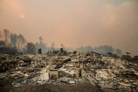 Rubble lines a residence leveled by the Loma fire along Loma Chiquita Road on Tuesday, Sept. 27, 2016, near Morgan Hill, Calif. More California residents were ordered from their homes Tuesday as a growing wildfire threatened remote communities in the Santa Cruz Mountains. (AP Photo/Noah Berger)