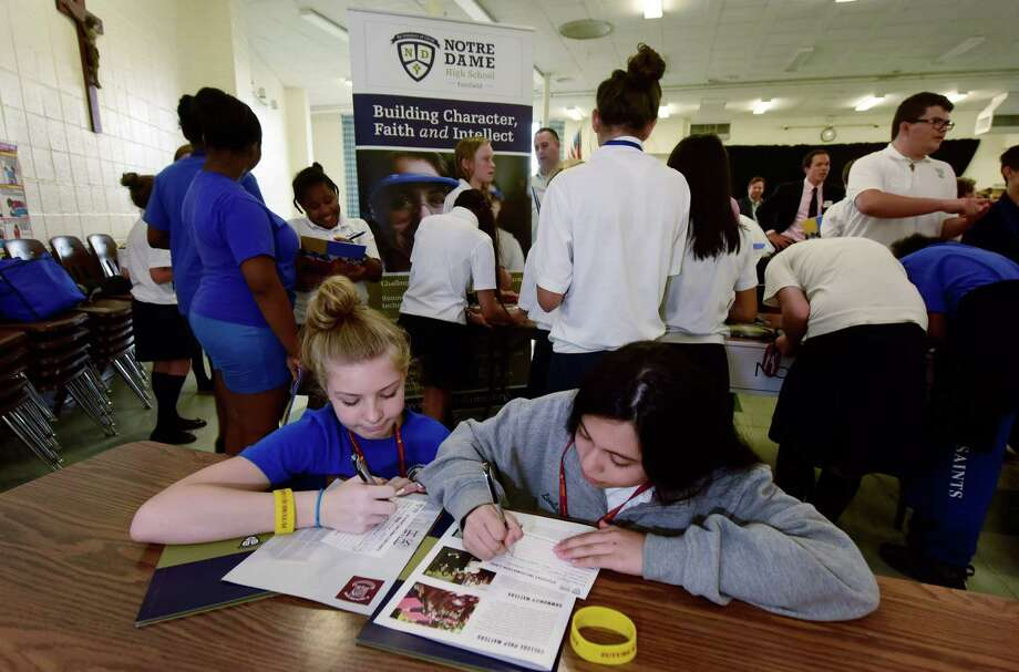All Saints Catholic School eighth graders, Carly Kirk and Megan Lombardo, fill out informal cards for Notre Dame High School in Fairfield as they spend an hour with their classmates Tuesday September 27, 2016, at the school's annual high school fair in Norwalk, Conn. where they collected information from 12 different area public and private high school's in an effort to help the students decide where they will spend the last four years of their education. Photo: Erik Trautmann / Hearst Connecticut Media / Norwalk Hour