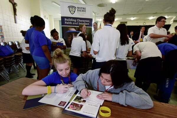 All Saints Catholic School eighth graders, Carly Kirk and Megan Lombardo, fill out informal cards for Notre Dame High School in Fairfield as they spend an hour with their classmates Tuesday September 27, 2016, at the school's annual high school fair in Norwalk, Conn. where they collected information from 12 different area public and private high school's in an effort to help the students decide where they will spend the last four years of their education.
