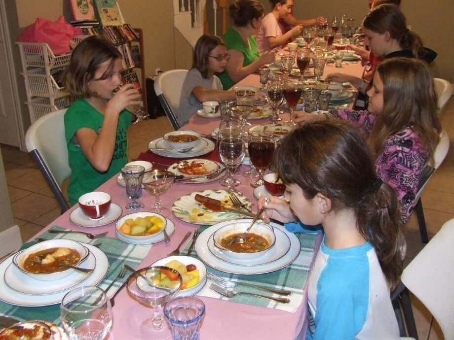 Girl Scouts, clockwise from left, Brianna Kirkland, Emily Sievers, Sarah McAdams and Elise Guerra enjoy course thrree of a seven course meal during their troop's etiquette dinner.