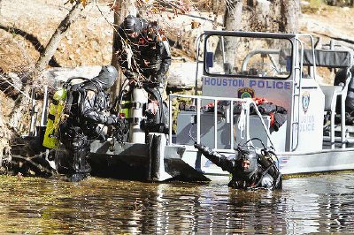 Divers from the Houston Police dive team work on equipment as a truck is pulled from Luce Bayou on Jan. 18. Houston Police recovered three vehicles presumed to be stolen from the bottom of the bayou after a local fisherman spotted the submerged cars and alerted authorities.