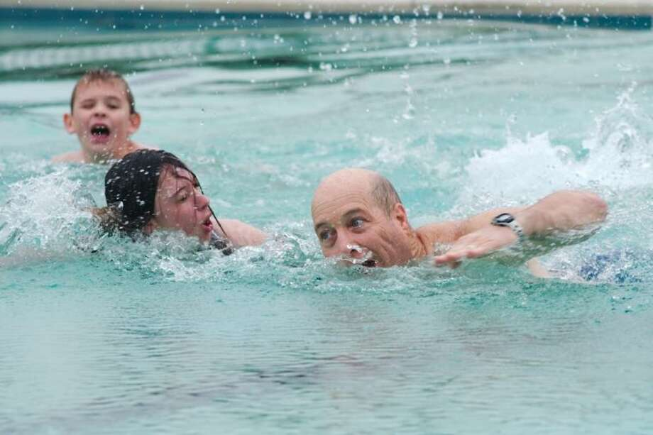 Tanner Williford watches and swims as Jalynn and Rusty Stewart race to the end of the pool during the annual Clear Lake Forest community Polar Bear Dare at the community pool Saturday, Jan. 5. / © 2012 Kirk Sides/Houston Community Newspapers