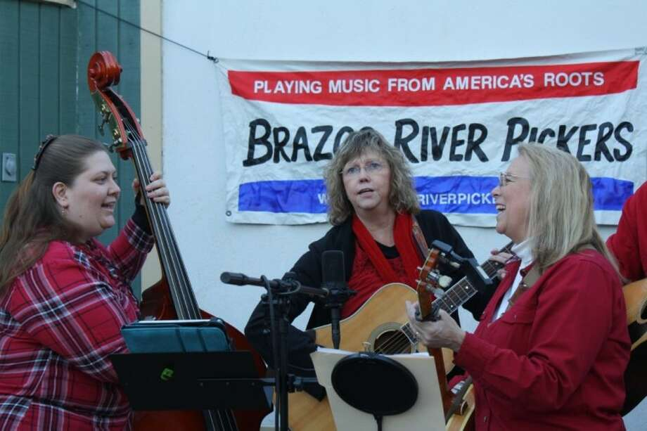 Bass player Sandy Rychlik, guitar player Anna Beavers and banjo player Heidi Witmer sing a song together at the Brazos River Pickers' January performance at the Brazos Bend State Park. Photo: Cory Stottlemyer