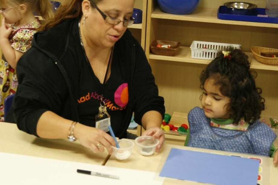 A Kingwood Montessori teacher helps a student get started on an art project in one of their classes.