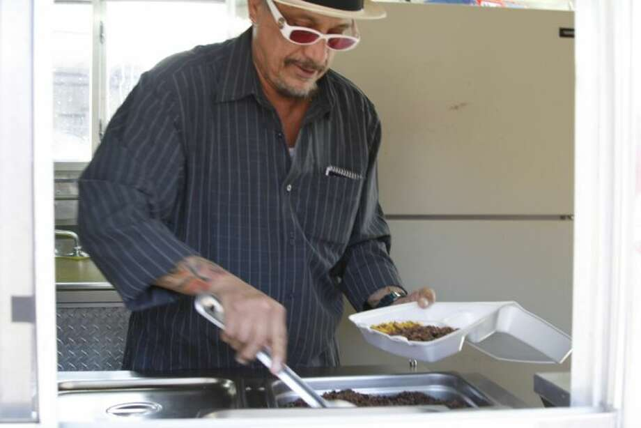 """Tony """"Papí"""" Castro prepares a dish for a customer at Papí's Kiosco in Porter."""