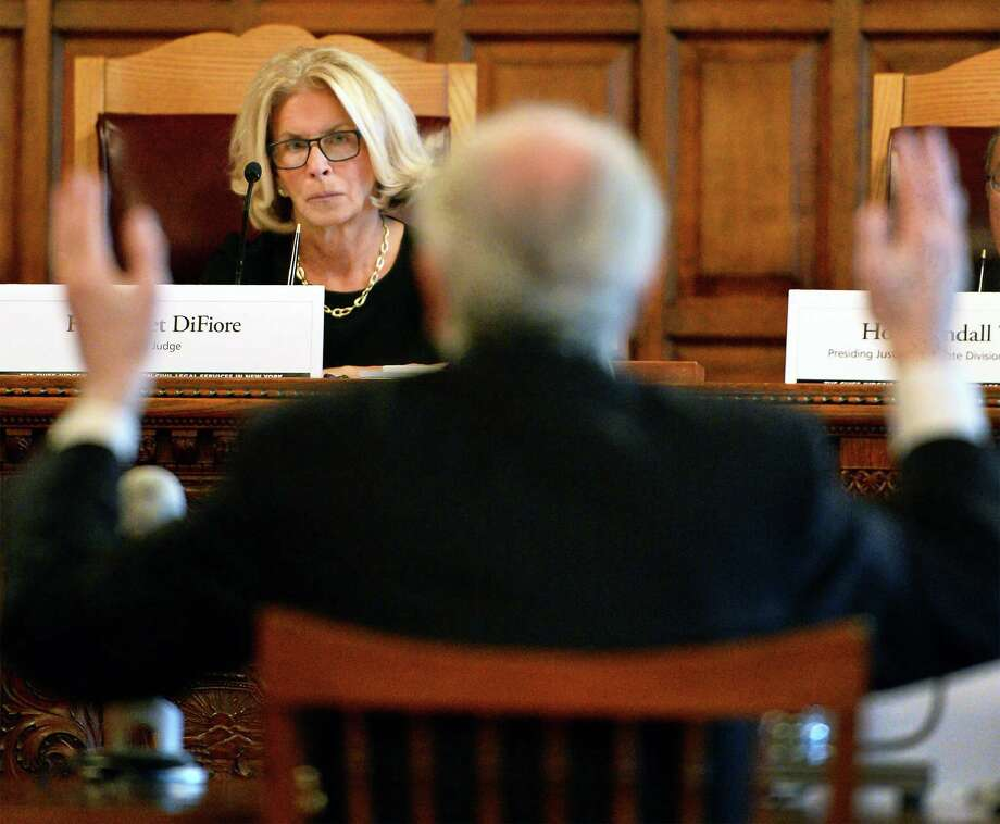 Chief Judge Janet DiFiore, left, listens as former New York Chief Judge Jonathan Lippman speaks before a statewide public hearing to evaluate the continuing unmet civil legal services needs in New York in the Court of Appeals Tuesday Sept. 27, 2016 in Albany, NY.  (John Carl D'Annibale / Times Union) Photo: John Carl D'Annibale / 40038184A