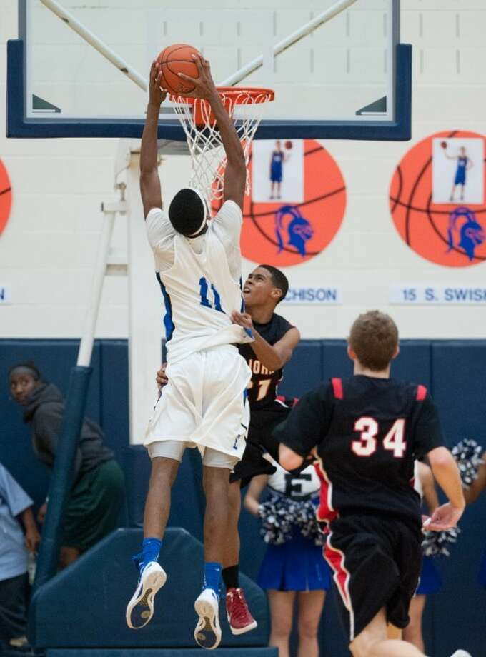 Brandon Williams dunks home two of his game-high 18 points as Episcopal edged Kory Haywood (21), Risher Randall (34) and rival St. John's, the first meeting since SJS won the SPC championship by a point at the buzzer. This year the tide turned the Knights' way, earningtheir revenge in a 51-50 win at EHS' Crum Court. (GulfCoastShots.com) Photo: Kevin B Long