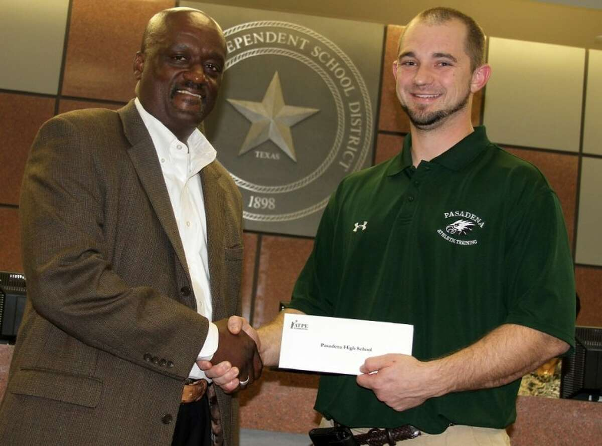 Larry Comer, representing the ATPE, presents a $2,500 grant check to Pasadena High's Jeremy Jackson.