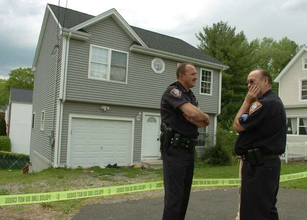 Shelton police officers in front of 119 Long Hill Avenue in Shelton, Conn., the former home of Faisal Shahzad, on Tuesday May 04, 2010. Shahzad, a suspect in the attempted bombing in Times Square Saturday night was taken into custody late Monday by FBI agents and New York Police Department detectives while trying to leave the country. Photo: Christian Abraham / Connecticut Post
