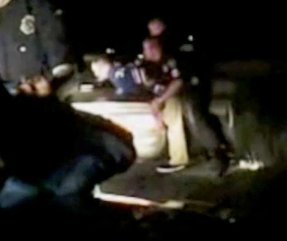 Cleveland police officers Paul Lowrey and Kevin Potter (in background) lean a Houston man, Chad Wayne White, over a patrol car before searching him. Prior to this, Lowrey reportedly jabbed his flashlight into White's abdomen. The incident is now under review by Cleveland Police Department administrators and city officials to see if the use of force was acceptable in this situation.
