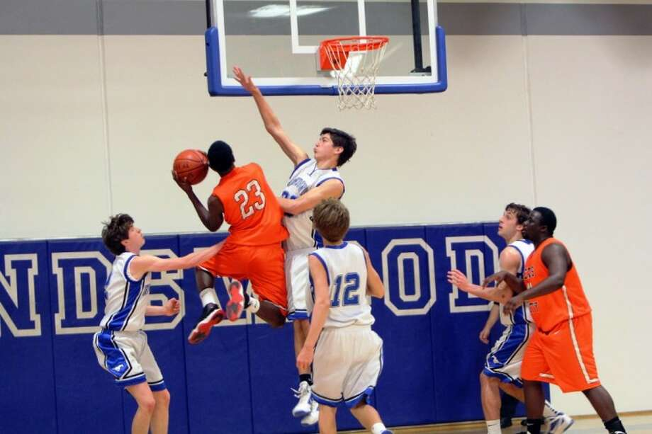 Texas City's Keenan Bell goes up against Friendswood's Kelby Schimming in a District 24-4A basketball game last week. The Mustangs won the game to solidify their playoff position. Photo: MIKE WOOLLEY