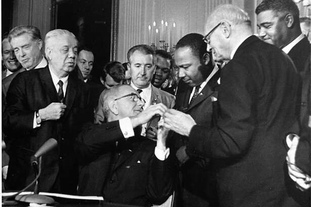 The Rev. Martin Luther King, third from right, head of the Southern Christian Leadership Conference, was among national figures present on July 2, 1964, as President Lyndon B. Johnson signed the Civil Rights Bill. After King's assassination, LBJ had to address racial unrest far worse than we are seeing today. It is part of his legacy.