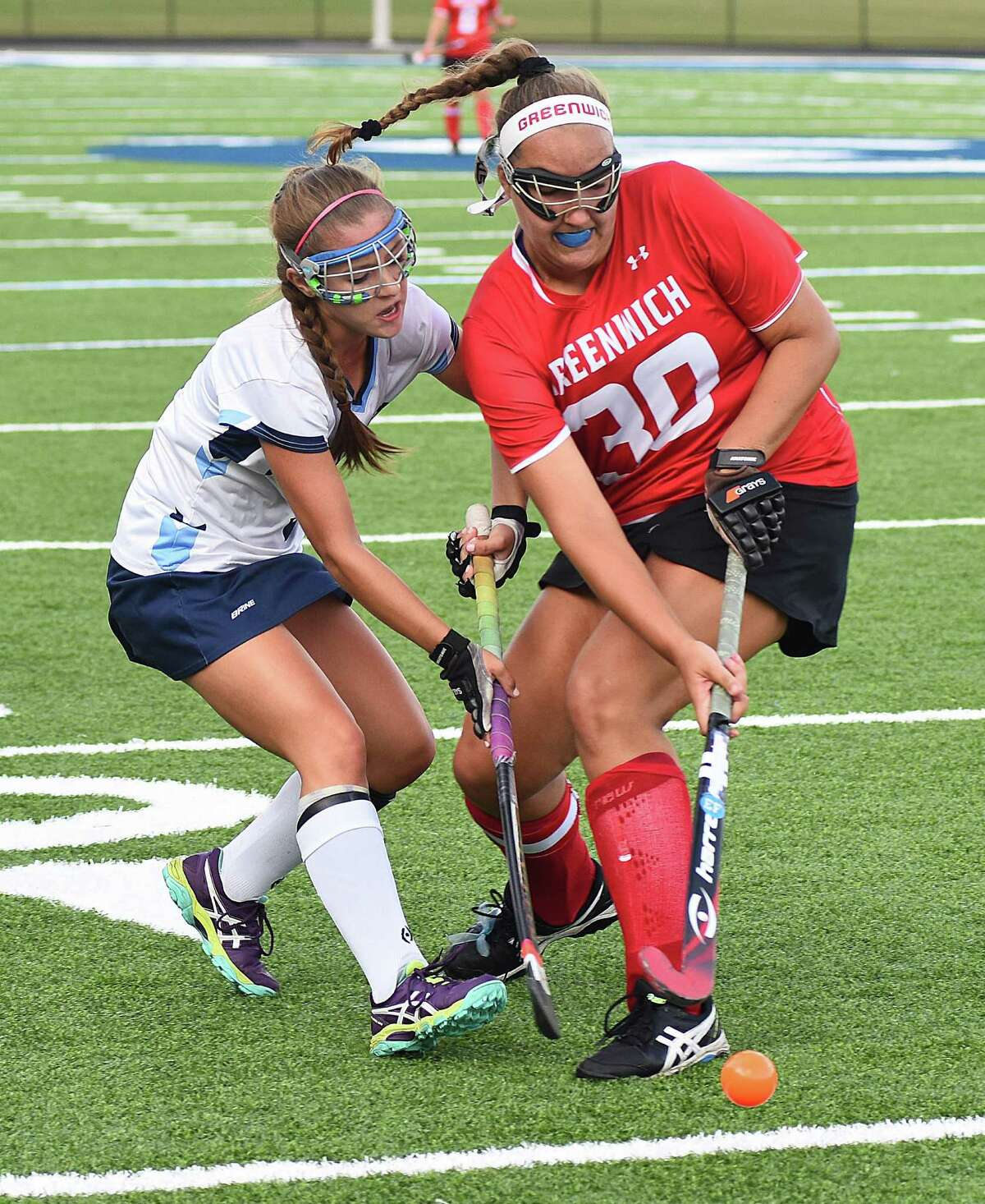 Wilton's Emma Rosen, left, and Greenwich's Emily Anderson come together to play a ball during Tuesday's FCIAC field hockey game at Fujitani Field in Wilton. The host Warriors defeated the Cardinals 4-1.
