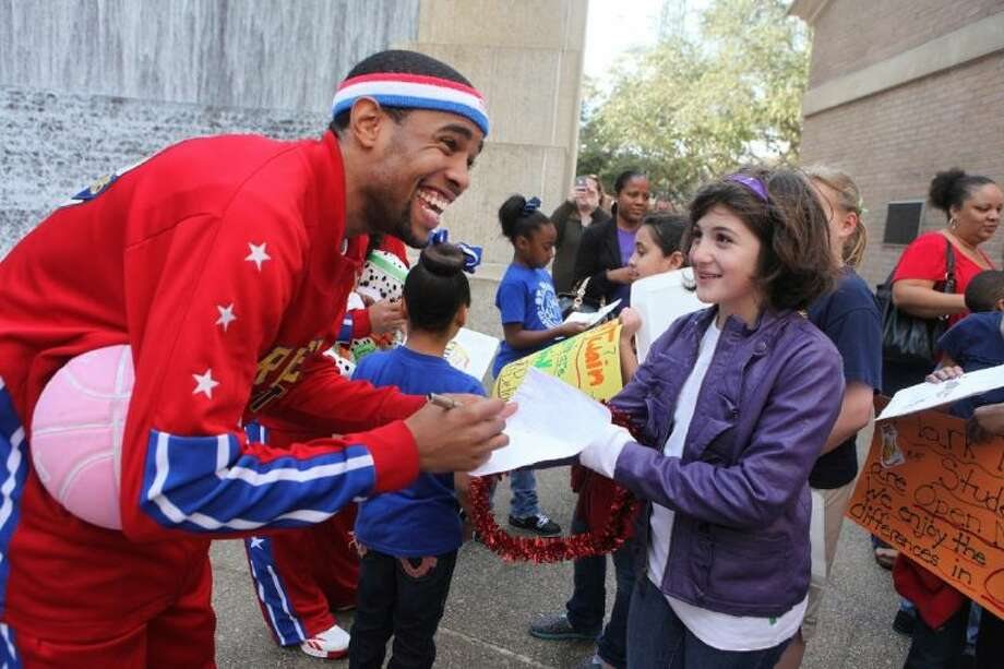 Harlem Globetrotter Cheese Chisholm signs an autograph for Lilly Knipe of Mark Twain Elementary School in Houston in front of the Gerald D. Hines Waterwall.