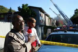 Sahal Mohamed holds his son Yusuf, 1, as fire crews work to extinguish a three-alarm fire that started in the Lam Bow apartment complex in the Delridge neighborhood in West Seattle, Tuesday afternoon, Sept. 27, 2016.  Mohamed and his family live on the 3rd floor of the building and ran out after seeing smoke rising from their bedroom floor.
