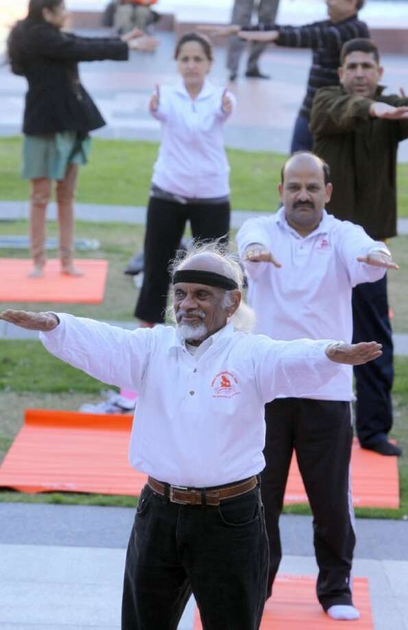 M.D. Shintri (front) warms up for the Yogathon along with others at the Sugar Land Town Square on Saturday, Jan. 28, 2012.