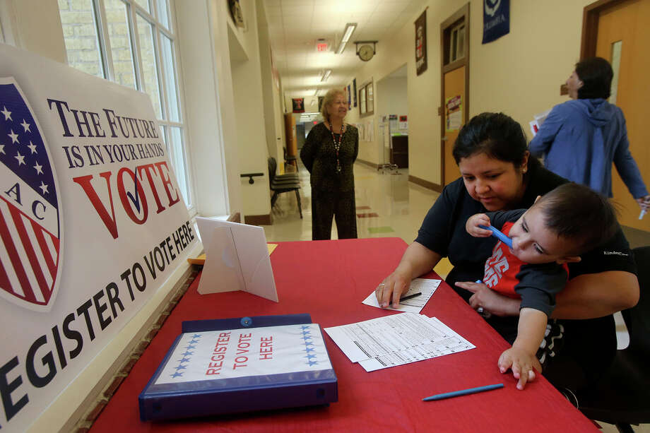 Juanita Vargas (right) holds her son Viggo Vargas, 18 months, while she fills out a voter registration card at Hawthorne Academy on Josephine street. Tuesday September 27, 2016 is National Voter Registration Day. Vargas said she was taking a parenting class at Hawthorne Academy so she decided to register while she was there. Standing in the backgound (smiling) is Mary Hogan with the League of United Latin American Citizens. Photo: John Davenport, Staff / San Antonio Express-News / ©San Antonio Express-News/John Davenport