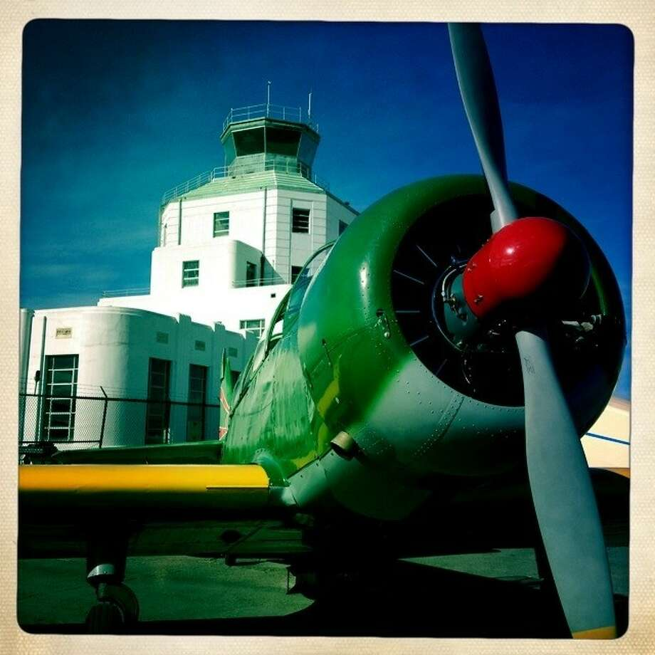 A World War II era Japanese plane with the terminal in the background