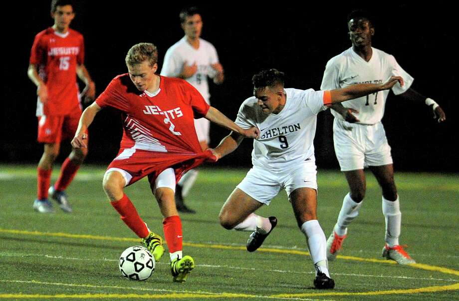 Shelton's Isajiah Robles, right, snags the jersey of Fairfield Prep's Briggs Palmer as he moves the ball during boys soccer action in Shelton, Conn., on Tuesday Sept. 27, 2016. Photo: Christian Abraham / Hearst Connecticut Media / Connecticut Post