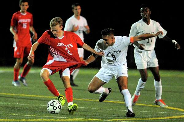 Shelton's Isajiah Robles, right, snags the jersey of Fairfield Prep's Briggs Palmer as he moves the ball during boys soccer action in Shelton, Conn., on Tuesday Sept. 27, 2016.
