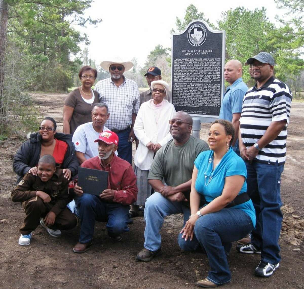 Descendents of the family pose in front of the historical cemetery marker commemorating the lives of William