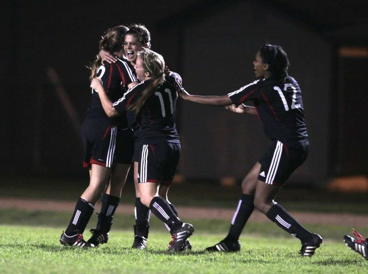 Austin's Marianna Hadjiloizou (center) is hugged by her teammates after she scored the winning goal during a shootout at the end of Friday's game against Austin. (Photo by Alan Warren)