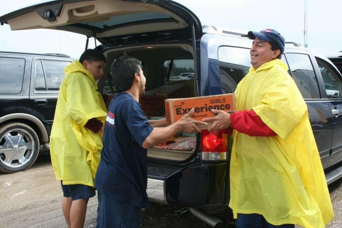 Volunteers help load cookies.