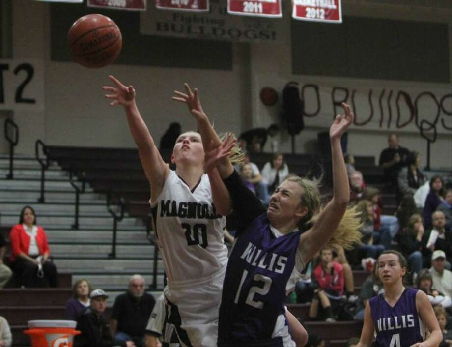 Magnolia's Caitlin Lawrence gets off a shot after being fouled by Willis post Haley Sellers on Friday at Magnolia High School. Photo: Jason Fochtman