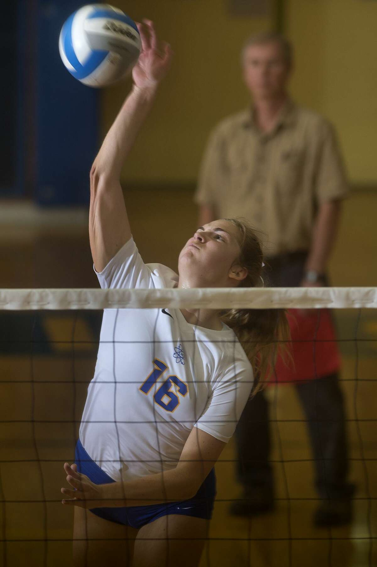 Midland High's Ellie Jensen spikes the ball in the second set of the Tuesday evening match against Heritage High School. The Chemics came back to win the win the match after losing the first two sets 24-26, 21-25, 25-17, 25-18, 15-7.