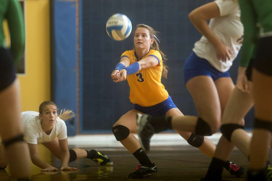 Midland High's Julia Gross digs up a spike from Heritage High School Jenna Nowaczyk in the third set of the Tuesday evening match. The Chemics came back to win the win the match after losing the first two sets 24-26, 21-25, 25-17, 25-18, 15-7. Photo: Brittney Lohmiller/Midland Daily News