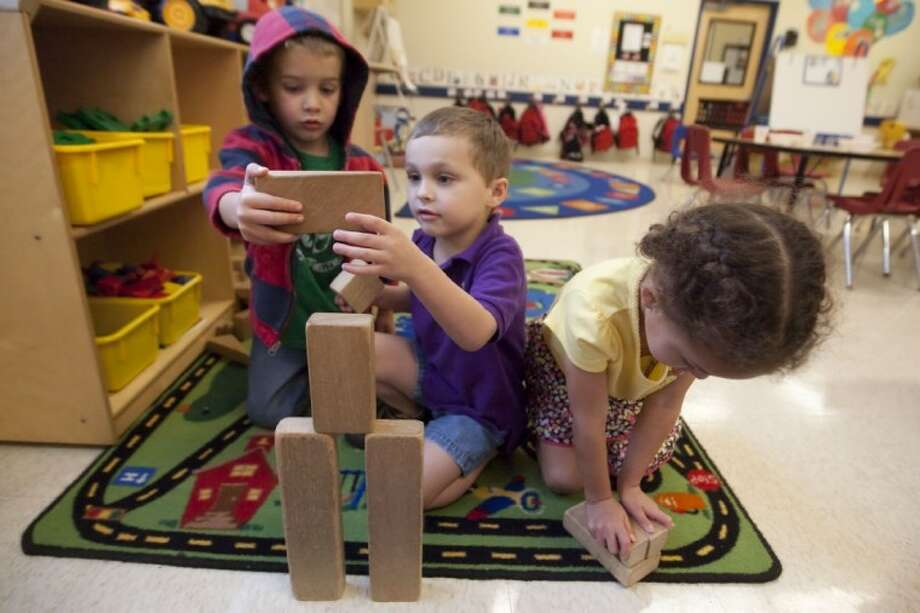 Aidan O'Neill, Mitchell Waindell, and Ava Matthews play with block at the Primrose School of Spring-Klein on Friday. Photo: Karl Anderson