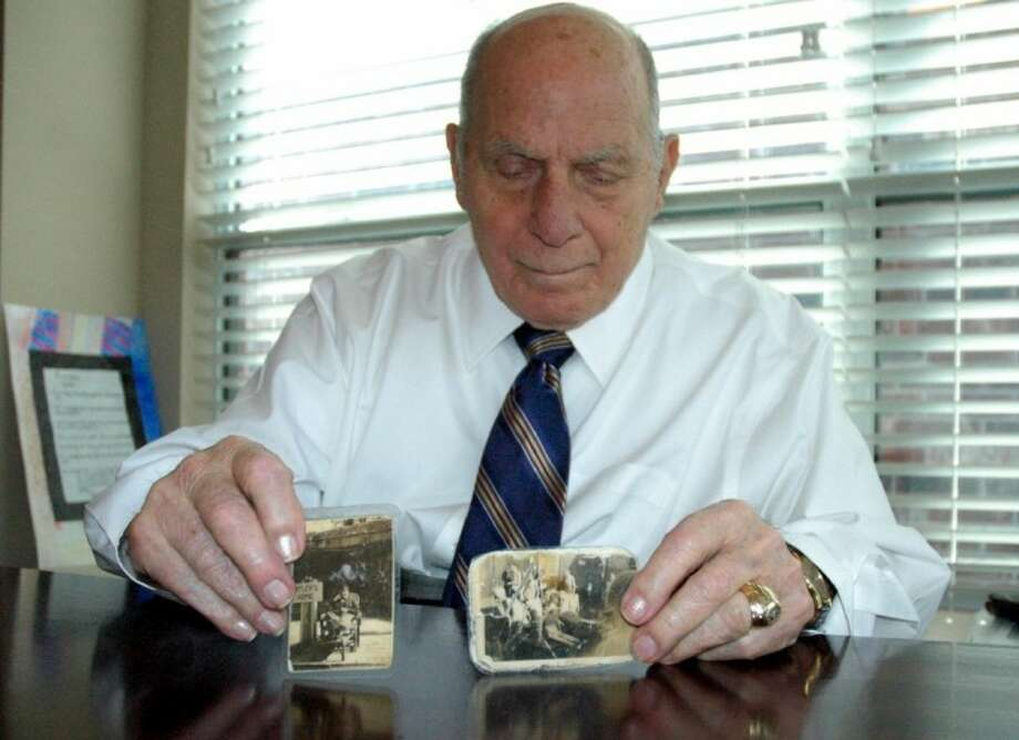 "Brig. Gen. Mike P. Cokinos (Ret.) holds a couple of photographs he's carried with him since World War II. The one on the left shows him reclining near a sign that reads ""Hitler's Home"": the other is a photo of emaciated Polish prisoners liberated by Cokinos' unit from a German concentration camp. Photo: Rusty Graham"