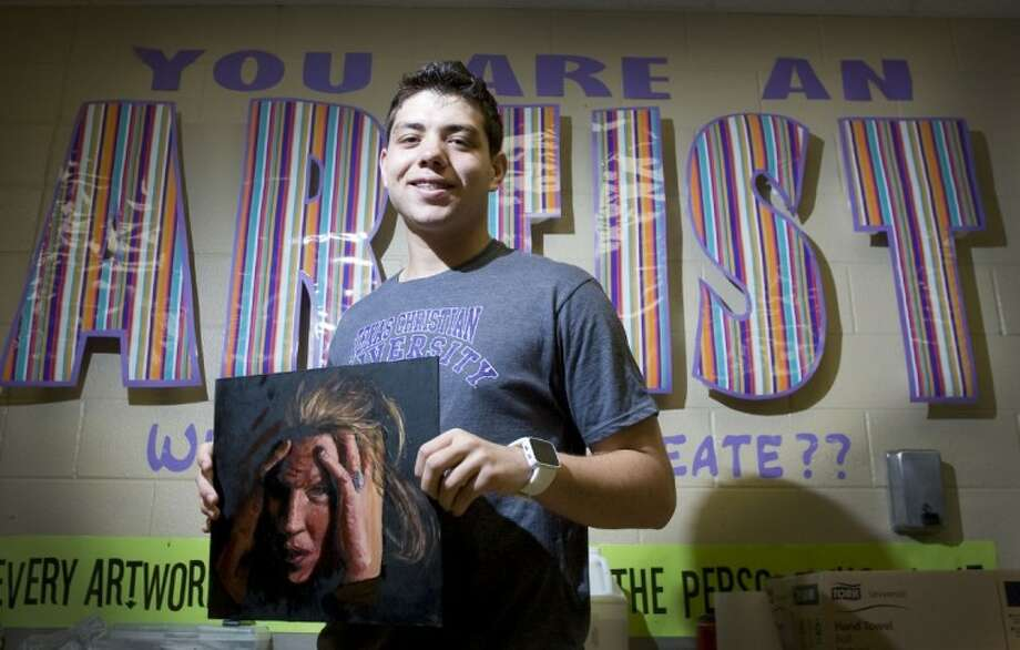 Magnolia West High School student Barry Carter holds a recent painting he drew. Photo: Staff Photo By Eric S. Swist