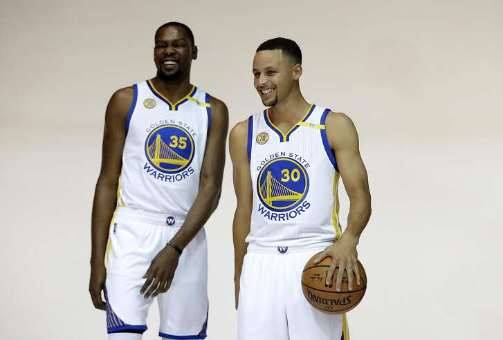 Golden State Warriors' Kevin Durant, left, and Stephen Curry pose for photos during NBA basketball media day Monday, Sept. 26, 2016, in Oakland, Calif. (AP Photo/Marcio Jose Sanchez)