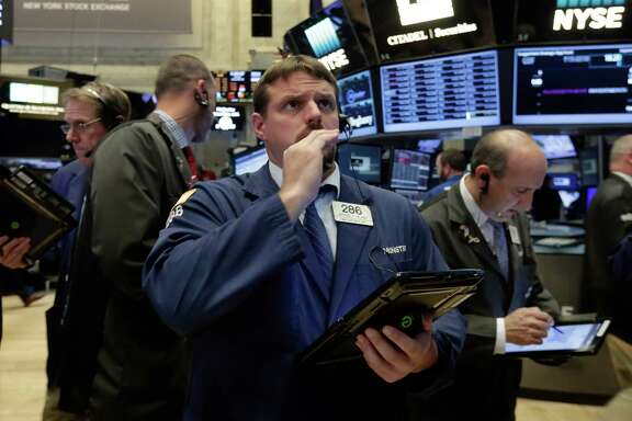 FILE - In this Monday, Sept. 26, 2016, file photo, trader Michael Milano, center, works on the floor of the New York Stock Exchange. European stocks faltered Tuesday, Sept. 27, as investors worried over Deutsche Bank's outlook, a big decline in oil prices and a sharp downgrade in global trade predictions. The reaction in markets to the first U.S. presidential debate of this campaign was fairly minimal. (AP Photo/Richard Drew, File)