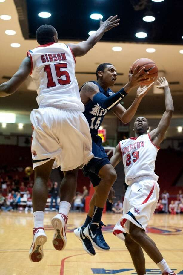 Rice's Julian DeBose finds a route for a layup between UH's Leon Gibson and Jonathon Simmons in the firsthalf. The Owls trailed by 13 initially but prevailed 79-71 in Conference USA action. (GulfCoastShots.com) Photo: Kevin B Long