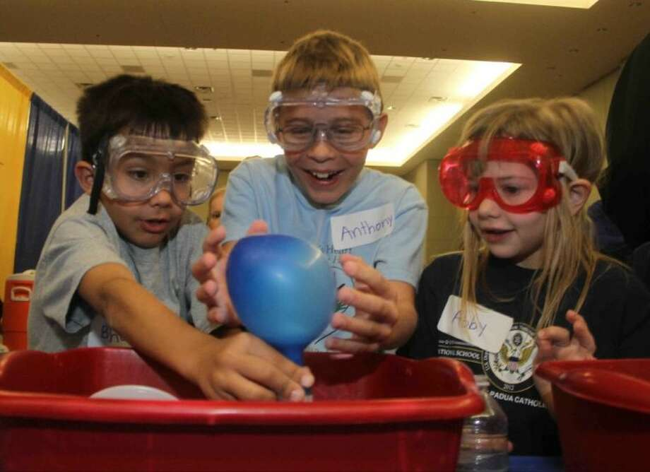 St. Anthony of Padua students Bishop Moorman, left, Collin Dufrene and Abby Stofer react as a balloon inflates by itself during the annual SCI://TECH Expo at Lone Star Convention & Expo Center Saturday in Conroe. Students at St. Anthony recently learned about the states of matter, and the booth showed visitors how they could use vinegar and baking soda to inflate a balloon. Hundreds of students from local schools showed off their science and mathematics knowledge in competitions and for the general public. Go to HCNPics.com to see more photos from the event.