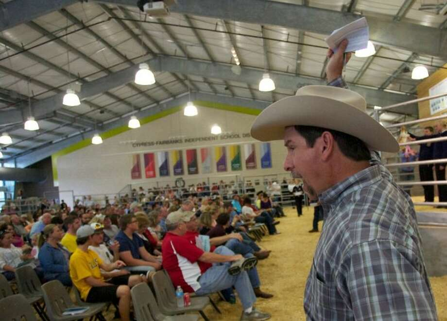 Auctioneer Tommy Miertschin signals a bid during Saturday's Cy-Fair ISD livestock auction at the CFISD Exhibit Center. For more photos from the annual sale, visit www.CypressCreekMirror.com or go to http://tinyurl.com/akd5e49. Photo: Staff Photo By Eric Swist