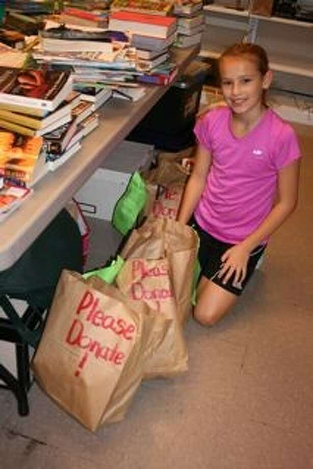 Katie Koehler, 11, of The Woodlands poses with bags collected during her book donation run on Jan. 12 and 13. Katie collected an unprecedented 478 books for the George and Cynthia Woods Mitchell Library in The Woodlands after launching her own campaign in her neighborhood, handing out grocery bags with flyers attached asking for any gently used books and magazines.