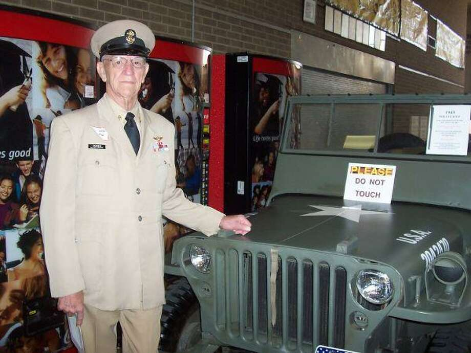 Korean War veteran Charles Grabein displays his 1943 Willys Jeep that he restored from the ground up. The original condition of the vehicle was a rusted heap that was pulled out of the woods in Moss Hill. Grabein served as a combat photographer during the Korean War and later had his own photography business.