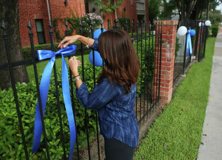 Tina Warren adjusts a ribbon Tuesday on the fence of the Oaks condominiums along Weslayan, near the scene of Monday morning's shootings.
