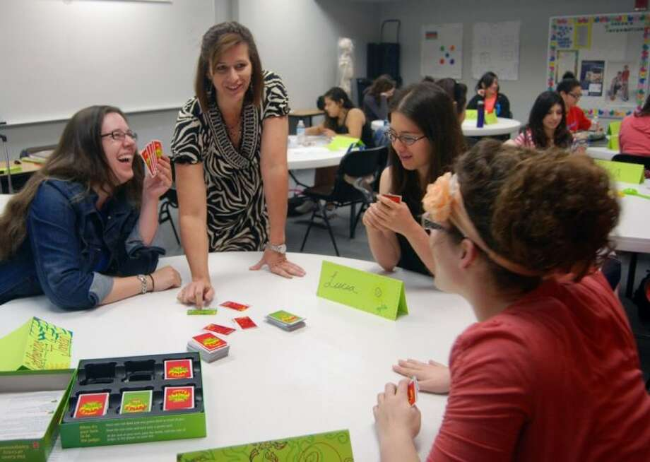 Teacher Education Coordinator Teresa Landers (center) shows students how board games can be incorporated in classroom exercises focusing on vocabulary and reading comprehension.