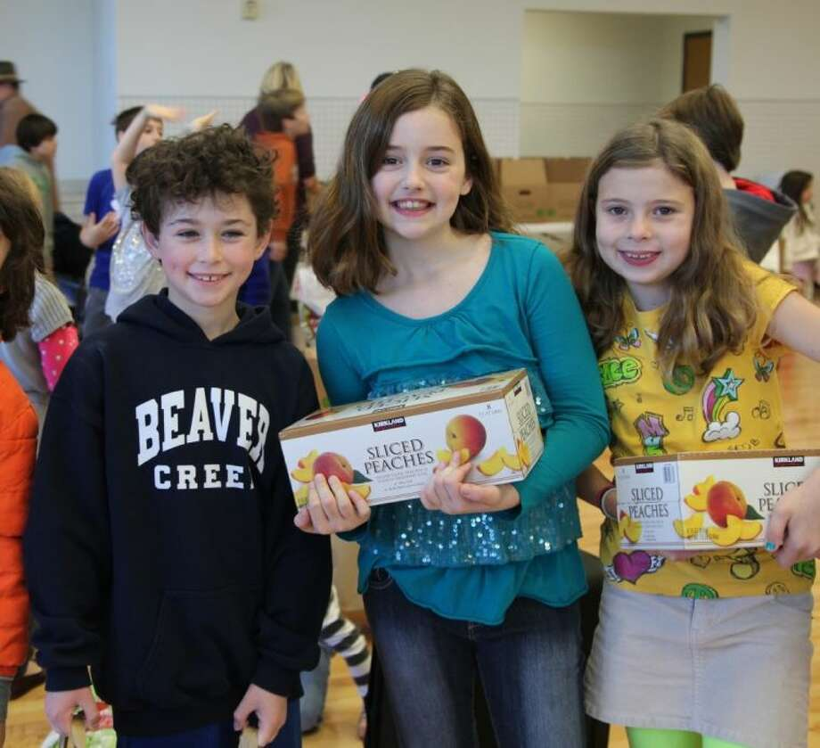 West University Elementary students Ryan Karkowsky, Emily Harrington, and Caroline Snider help sort donations for the Souper Bowl of Caring. The school collected nearly 30,000 pounds of food during the drive.
